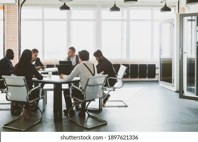 Group of young business people working and communicating while sitting at the office desk together with colleagues sitting. business meeting
