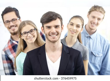 Group of young business people working with project. Young man smiling and looking at camera. Business team standing behind him