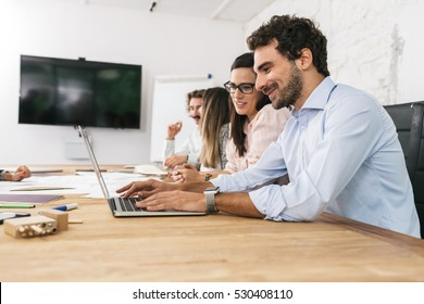 Group of young business people working at start-up in office with laptop