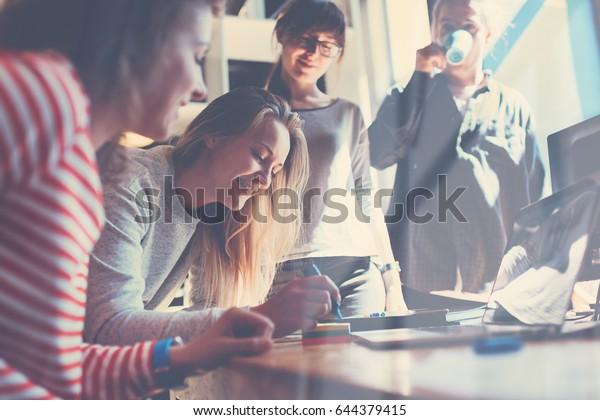 大きな共働きオフィスで共に働く若いビジネスマンのグループ。製品計画を説明するマーケティング部門。新しい起業会社。Windows反射効果