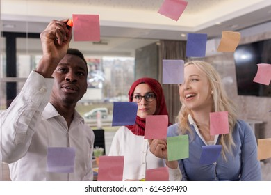 Group of young business persons are discussing ideas on glass wall with sticky notes