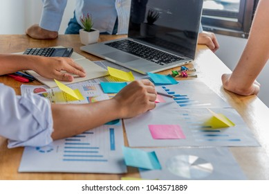 Group of young businessman talking and discussing about work or big project and pointing finger at the graph.