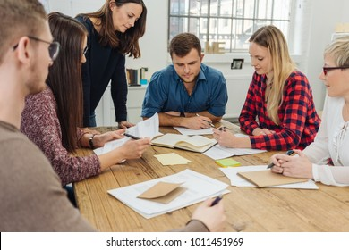 Group of young businesspeople brainstorming as they sit around a table in the office analysing paperwork and documents