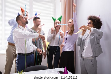 Group Of Young Businesspeople Celebrating New Year Party In Office