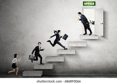 Group of young businesspeople compete on the stair by running toward the office door