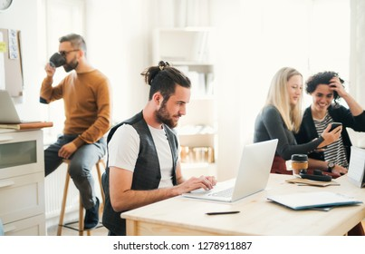 Group of young businesspeople with laptop working in a modern office.