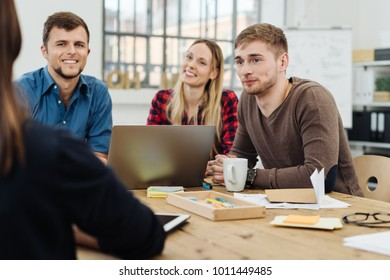 Group of young businesspeople in a staff meeting sitting grouped around a laptop computer listening to a manageress or team leader