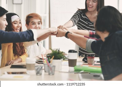 Group of young businesspersons fist-bumping in agreement in a meeting at office