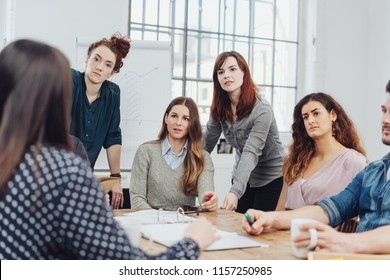 Group of young businesswomen listening attentively during a meeting in the office in an over the shoulder view