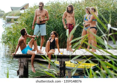 Group of young Caucasian people drinking beer on a wooden pier.