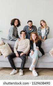 Groupe de jeunes hommes et femmes joyeux et amicaux en vêtements de nuit vous regardant tout en vous relaxant sur un canapé confortable