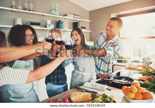 Group of young cheerful friends cheering with wine glasses while cooking some tasteful food at kitchen.