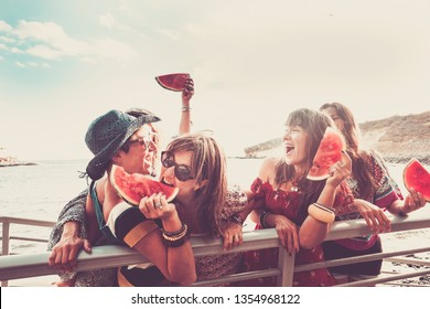 Group of young cheerful girls have fun together eating a watermelon all together at the beach with ocean and clear sky in background - friendship and playful people in outdoor leisure activity