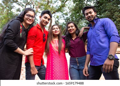 Group of young cheerful Indian people bonding to each other and smiling