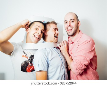 Group of young cheerful people making facial expression in photobooth on birthday party isolated on white background