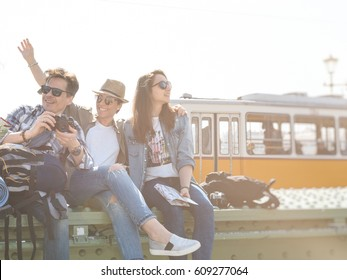 a group of young and cheerful travelers, enjoying the beautiful sunny day during a break, sitting on a bridge