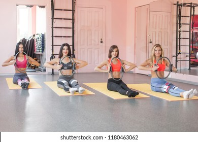 Group of young cheerful women making pilates exercises with fitness rings