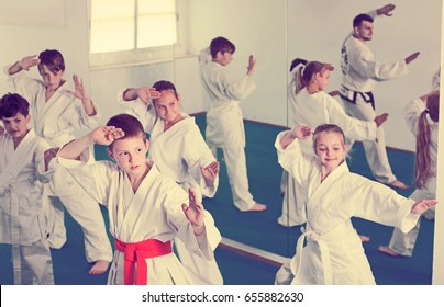 Group of young children doing karate kicks with male coach during karate class
