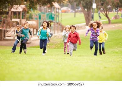 Группа маленьких детей бегут к камере в парке