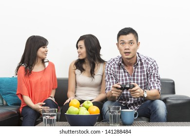 Group of Young Chinese friends playing video games at home