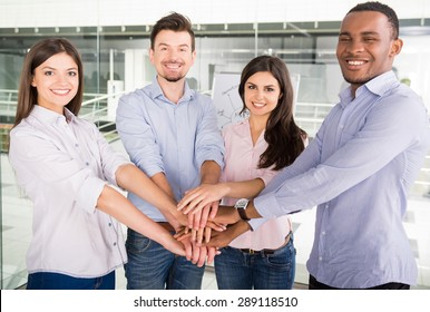 Group of young colleagues dressed casual standing together in modern office and smiling to camera.