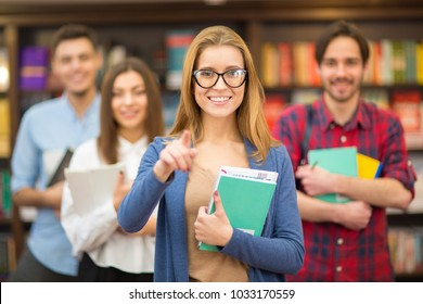 Group of young college students posing at the library gorgeous cheerful woman pointing at you copyspace choosing picking education gesturing achieving confidence project bookstore smart.