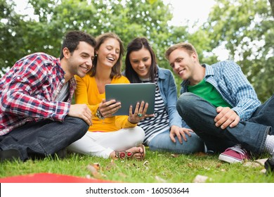 Group of young college students using tablet PC in the park