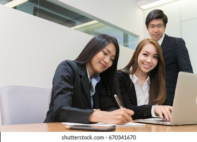 Group of young and confident Asia business man and woman working in modern office happily.