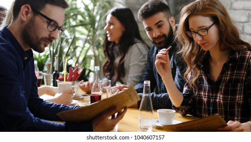 Group of young coworkers socializing in restaurant