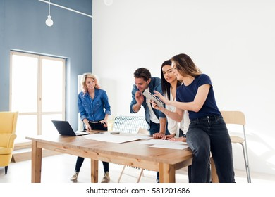Group of young coworkers using a digital tablet while brainstorming in the office