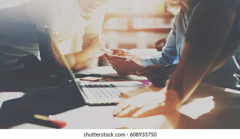 Group of young coworkers working together at modern office at sunset.Woman holding smartphone and talking with colleague about new startup project.Business people brainstorming concept.Visual effects