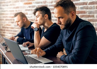 Group of young and creative IT people working in an office. Three programmers coding by the desk.
