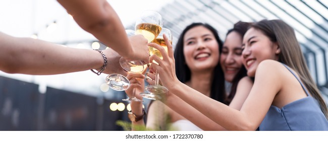 Group of young cute Asian girl gang best friends having party at rooftop restaurant. Girls drinking beer alcohol and toasting glass feeling happy enjoy, fun with smile face. Night lifestyle concept.