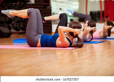 Group of young cute women working out and doing some crunches at a gym