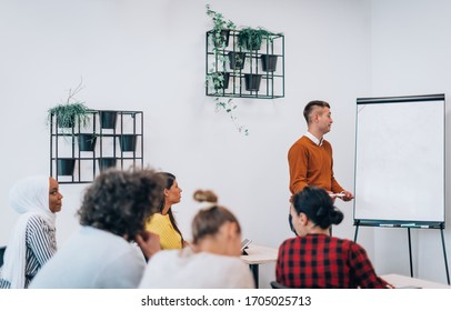 Group of young diverse people gathered together having a work presentation on whiteboard