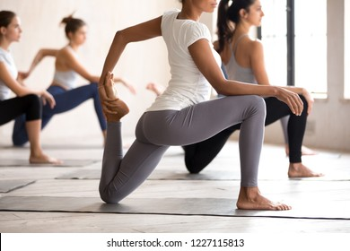 Group of young diverse sporty people doing yoga Horse rider exercise, anjaneyasana pose, working out indoor close up, active female students training at sport club studio. Well being, wellness concept