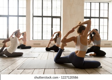 Group of young diverse sporty people practicing yoga, doing Eka Pada Rajakapotasana pose, working out indoor, mixed race female students training at sport club, rear view. Well being, fitness concept