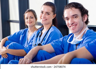 group of young doctors and nurses relaxing in hospital hallway during break