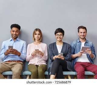 Group of young employees from different nations, sit together in ofiice as wait for job interview, use contemporary mobile phone and tablet computer, smile pleasantly, hope to make positive impression