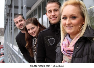 Group of young European students looking happy outdoors in a row