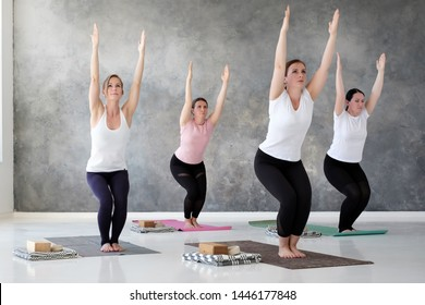 Group of young european woman doung utkatasana or chair pose at yoga class. Active lifestyle, wellness concept