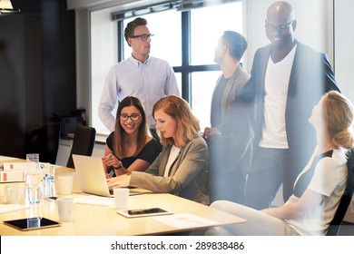 Group of young executives socializing in office conference room