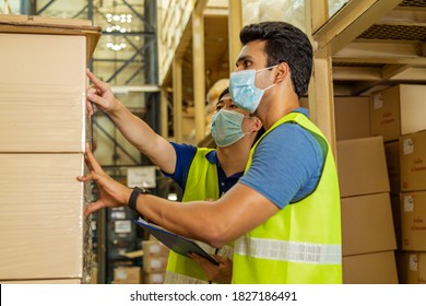 Group of young factory warehouse workers wearing a protective face mask while working in logistic industry indoor. Asian and Indian ethnic men checking item order during Coronavirus Covid 19 pandemic