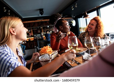 Group of young female friends having fun in restaurant, talking and laughing while dining at table.