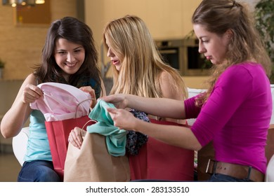 Group of young female friends looking at new clothes