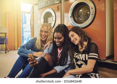 Group of young female friends sitting on a laundromat floor together laughing and using a cellphone