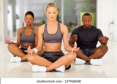 group of young fit people meditating in a gym class