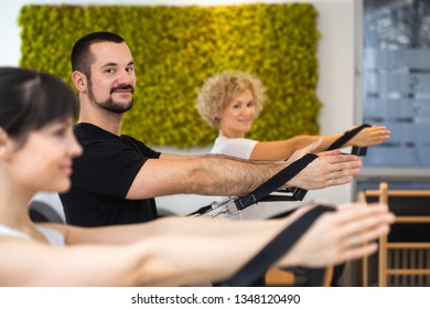 group of young fitness people in sportswear doing yoga stretching on Pilates reformer, together in class at gym. training,healthy life style concept