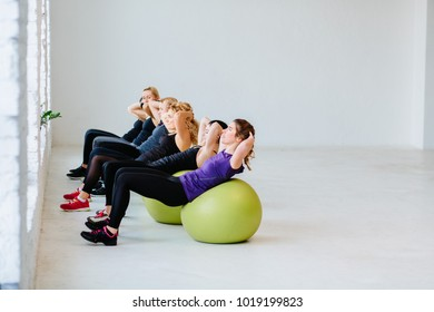 Group of young fitness woman doing abs crunches with a ball in the gym. Teamwork, friendship and healthy lifestyle concept. Copy space