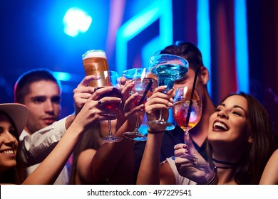 Group of Young friendly people toasting in night club or bar